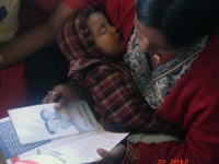A mother observing booklets on child rights protection and promotion