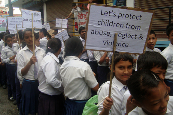 A student holding placard at children's day rally organized by child club
